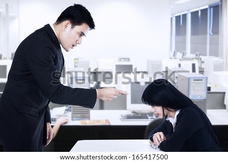 A businessman is bullying his subordinate in the office - stock photo