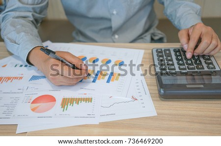 A businessman is calculating the company financial profit by using a calculator.
