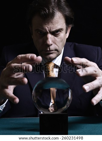 A businessman is consulting a crystal ball to foretell the future - stock photo