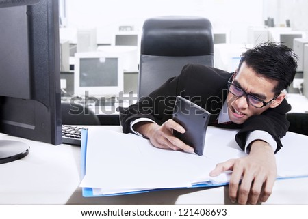 A businessman is holding a calculator worrying about paying bills and making profit