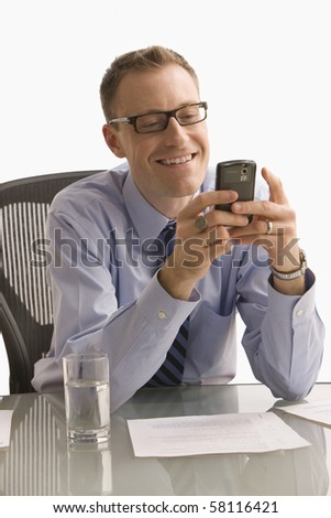A businessman is seated at a desk in an office and is texting on a cell phone.  Vertical shot.  Isolated on white.