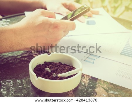 A businessman is seriously working with mobile phone looking at graph paper with  cigarette butt in ashtray, selective focus of business and financial working concept. - stock photo