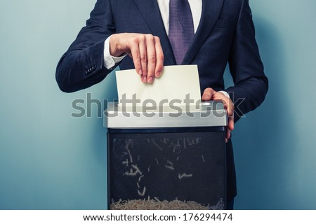 A Businessman is shredding important documents - stock photo
