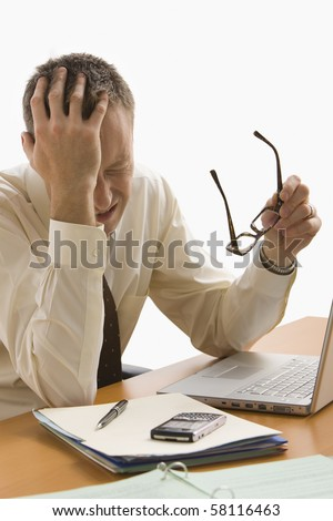 A businessman is stressed out at his work desk.  He has his glasses off and eyes closed.  Vertical shot.  Isolated on white.