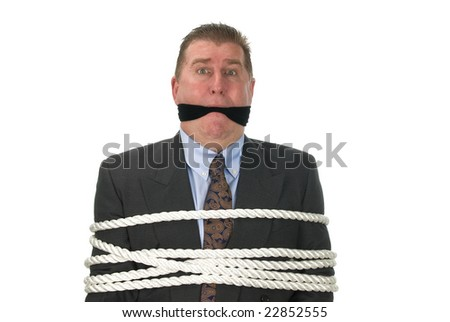 A businessman is tied up by angry co-workers. - stock photo