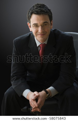A businessman is wearing glasses and smiling while sitting and looking confident. Vertical shot. - stock photo