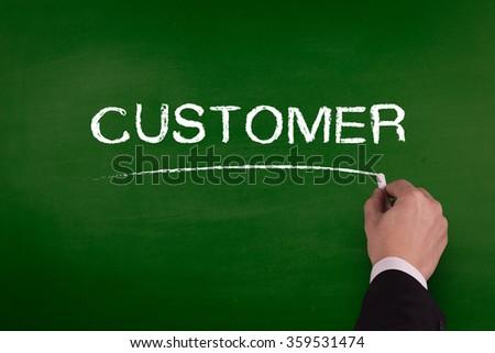 A businessman is writing CUSTOMER concept on blackboard. - stock photo