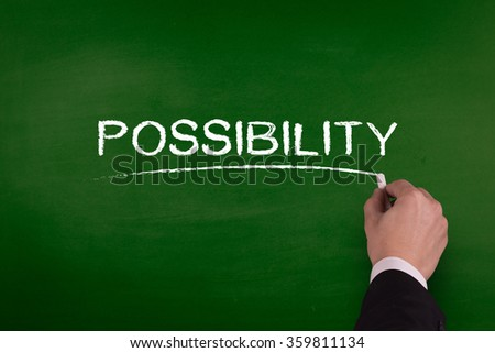 A businessman is writing POSSIBILITY concept on blackboard. - stock photo