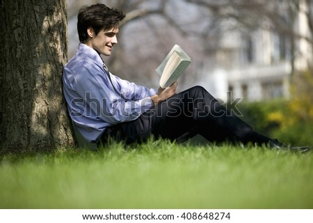 A businessman leaning against a tree, reading a book - stock photo