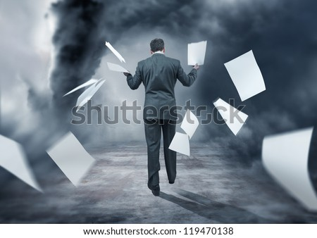 A Businessman Letting go of paperwork in a storm - stock photo