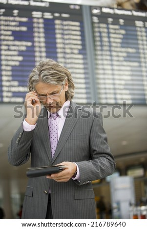A businessman looking at his boarding pass. - stock photo