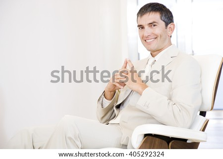 A businessman looking happy and relaxing in a chair - stock photo