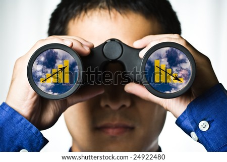 A businessman looking through binoculars, seeing conflicting trends in earnings prediction, can be used for business vision or business prediction concept - stock photo