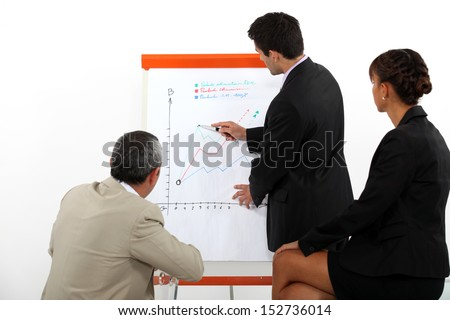 A businessman making a presentation to his coworkers. - stock photo