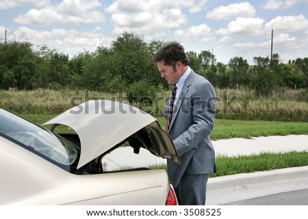 A businessman on a road trip, opening his trunk.