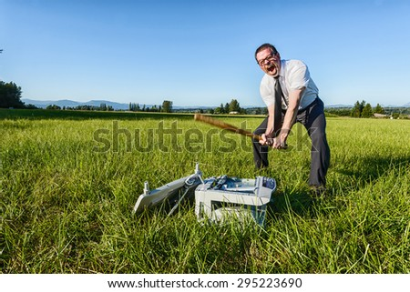 A businessman or IT professional beats on a laser printer - stock photo