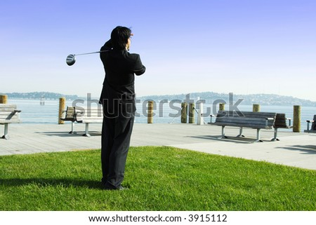 A businessman playing golf during his business break - stock photo