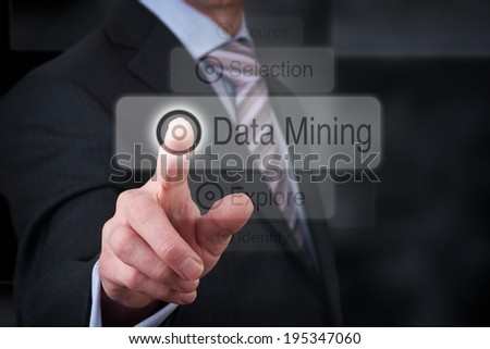 A businessman Pointing to a data mining button on a clear screen.