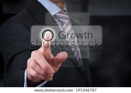 A businessman Pointing to a growth button on a clear screen.