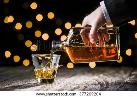 a businessman pouring whiskey into a glass.