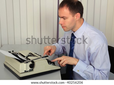 A businessman prints to the old printing typewriter.