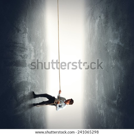 A businessman pulling a rope to climb - stock photo