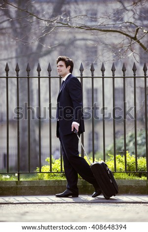 A businessman pulling his suitcase - stock photo
