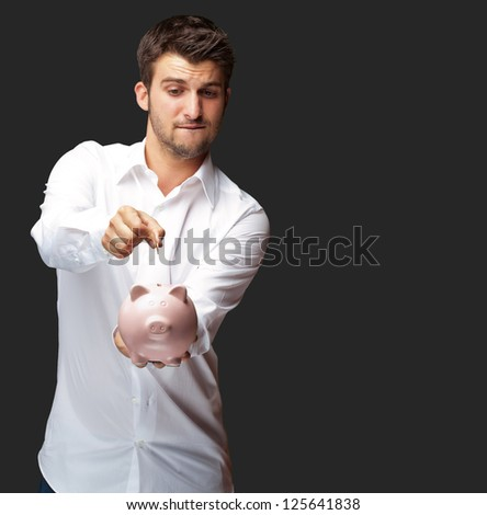 A Businessman Putting A Coin Into A Pink Piggy Bank Isolated On Black Background - stock photo
