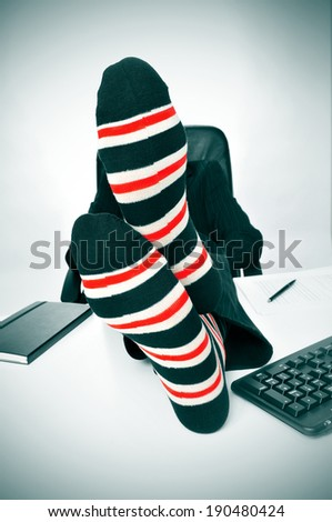 a businessman relaxing in the office with his feet on the desk - stock photo