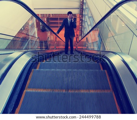 a businessman riding an escalator toned with a retro vintage instagram filter effect - stock photo
