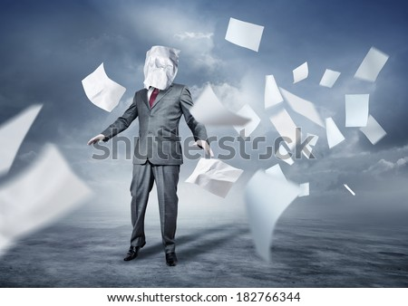 A businessman's face covered in paperwork. Business concept.