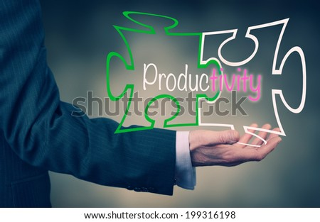 A Businessman's hand holding the word Productivity. - stock photo
