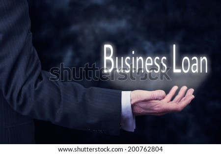 A businessman's hand holding the words, Business Loan. - stock photo