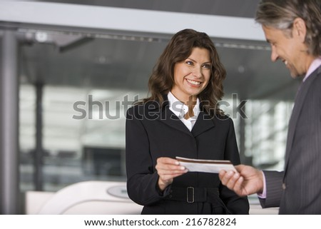 A businessman showing his boarding pass at the check in counter.