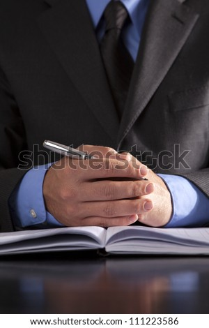 A businessman sits at a desk with a notebook and a pen in his hand ready to start a meeting.