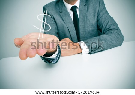 a businessman sitting in a desk showing a drawn dollar sign in his hand - stock photo