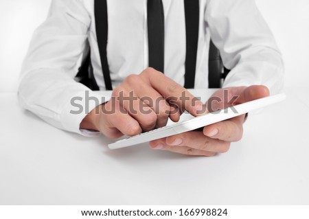 a businessman sitting in a desk using a tablet computer - stock photo