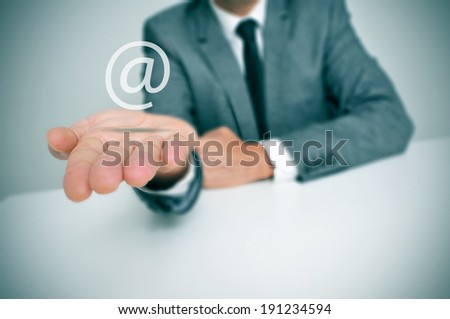 a businessman sitting in a desk with an at sign in his hand, depicting the concept of e-mail service - stock photo