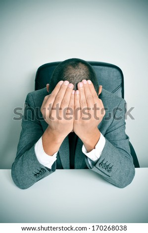 a businessman sitting in a desk with his hands in his head - stock photo