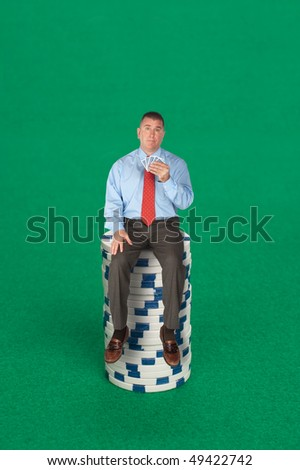 A businessman sitting on a stack of poker chips with a five card hand dealing with risk, success, chance or strategy.
