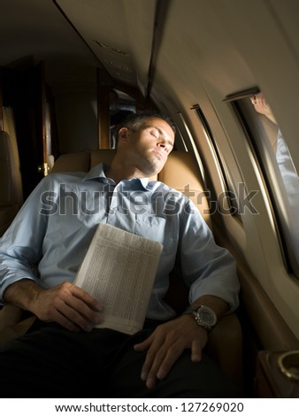 A businessman sleeping in an airplane - stock photo