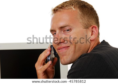 A businessman smiling at good news on the phone - stock photo