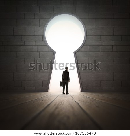 A businessman standing in a wall opening - stock photo