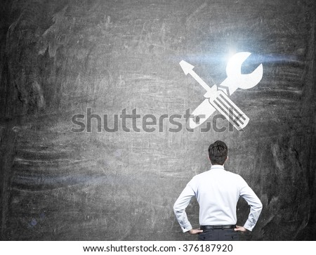 A businessman standing with hands on hips, a screwdriver and a wrench crossed are drawn on a blackboard over his head. Back view. Concept of fixing things. - stock photo