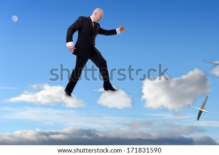 a businessman stepping on clouds - stock photo