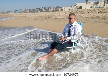 A businessman takes his office to the beach. - stock photo