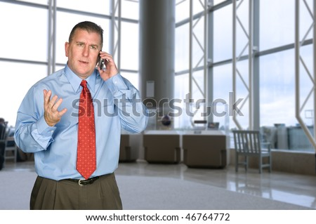 A businessman talking on his cell phone is not happy with the tone of the conversation. - stock photo