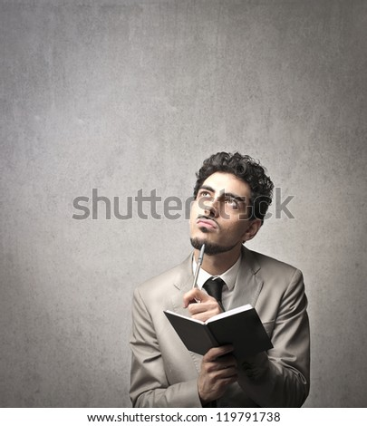 A businessman thinks while is writing on an agenda - stock photo