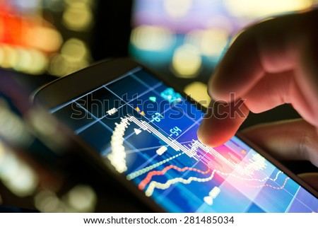 A businessman using a mobile phone to check stock market data. - stock photo