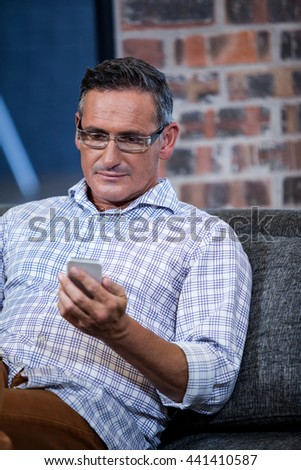 A businessman using cellphone in sofa